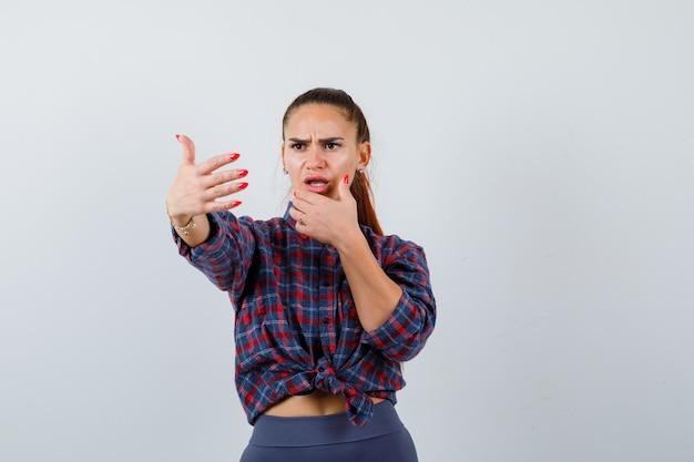 Jonge vrouw in geruit hemd, broek die uitnodigt om te komen en er angstig uitziet, vooraanzicht.