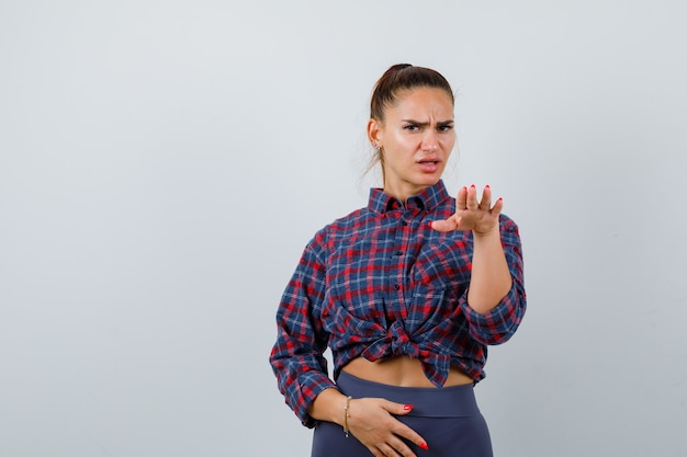Jonge vrouw in geruit hemd, broek met handpalm naar buiten gebarend om te stoppen en er serieus uit te zien, vooraanzicht.