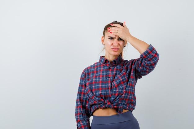 Jonge vrouw in geruit hemd die hoofd met palm vasthoudt en er pijnlijk uitziet, vooraanzicht.