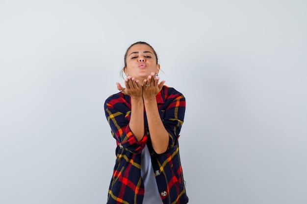 Jonge vrouw in geruit hemd die luchtkus blaast en er aantrekkelijk uitziet, vooraanzicht.