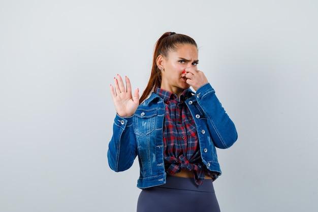Jonge vrouw in geruit hemd, jas, broek die in de neus knijpt vanwege een slechte geur en er walgelijk uitziet, vooraanzicht.