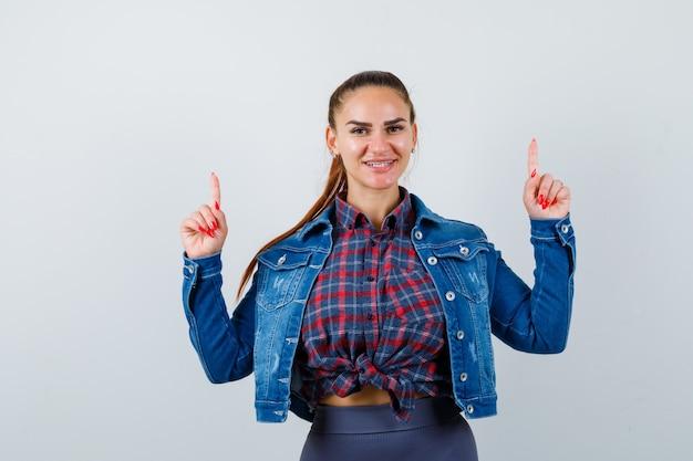 Jonge vrouw in geruit hemd, jas, broek die naar boven wijst en er charmant uitziet, vooraanzicht.