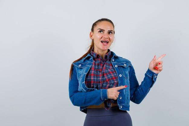 Jonge vrouw in geruit hemd, jas, broek die naar de rechterkant wijst en er gelukkig uitziet, vooraanzicht.