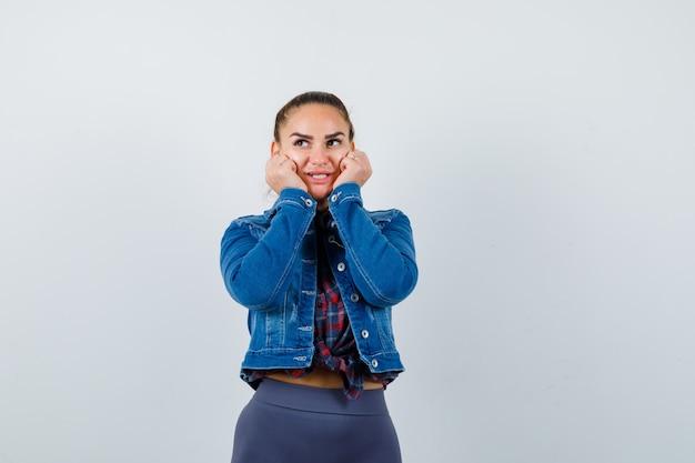 Jonge vrouw in geruit hemd, jas, broek met handen op de wangen en ziet er schattig uit, vooraanzicht.