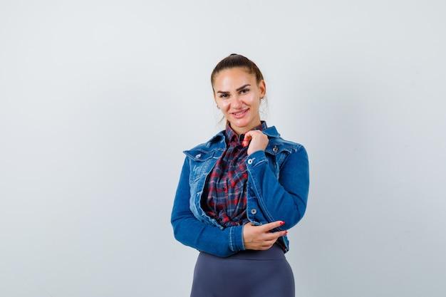 Jonge vrouw in geruit hemd, jas, broek poseren terwijl ze staan en er charmant uitzien, vooraanzicht.