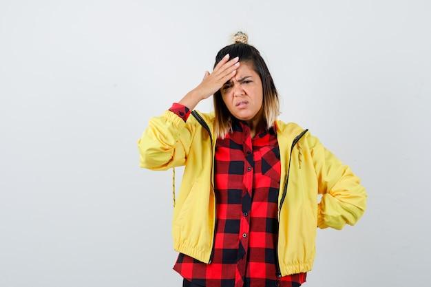 Jonge vrouw in geruit hemd, jas die hand op het voorhoofd houdt en er verontrust uitziet, vooraanzicht.