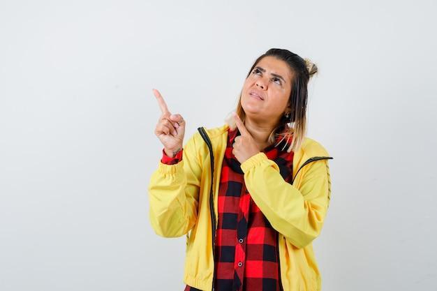 Jonge vrouw in geruit hemd, jas wijzend naar de linkerbovenhoek en peinzend kijkend, vooraanzicht.