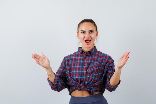 Jonge vrouw in geruit hemd spreidt handpalmen uit en kijkt geschokt, vooraanzicht.