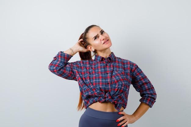 Jonge vrouw in geruit overhemd, broek met hand achter hoofd terwijl ze de hand op de heup houdt en peinzend kijkt, vooraanzicht.
