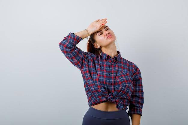 Jonge vrouw in geruit overhemd, broek met hand op voorhoofd en uitgeput, vooraanzicht.