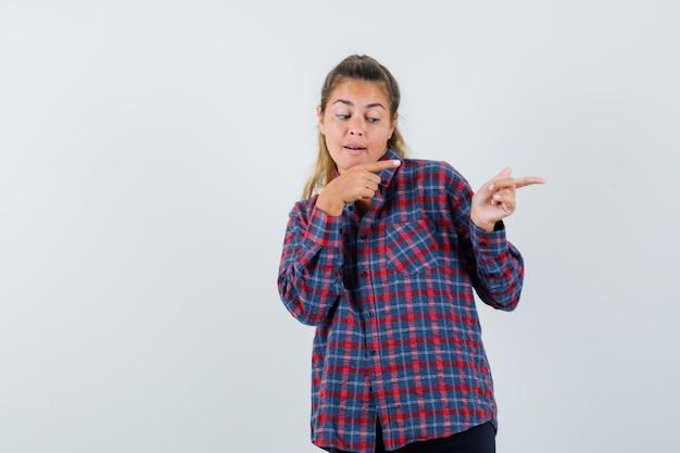 Jonge vrouw in geruit overhemd dat met wijsvingers naar rechts wijst en gelukkig kijkt
