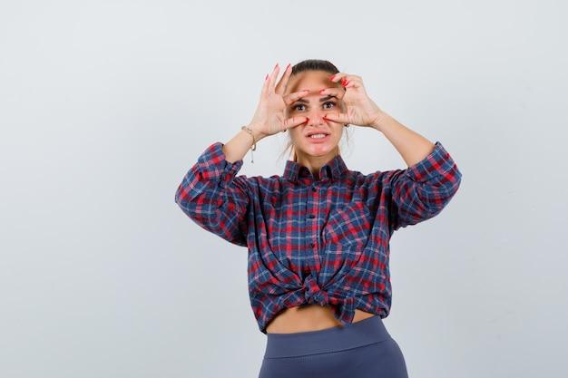 Jonge vrouw in geruit overhemd die door vingers kijkt en nieuwsgierig kijkt, vooraanzicht.