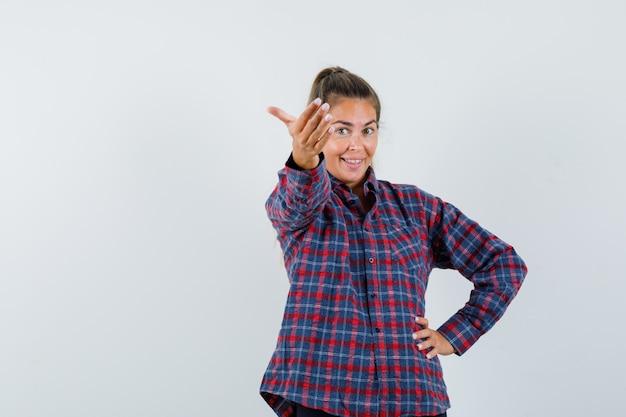 Jonge vrouw in geruit overhemd die hand op taille houden terwijl ze uitnodigt om te komen en er gelukkig uitziet
