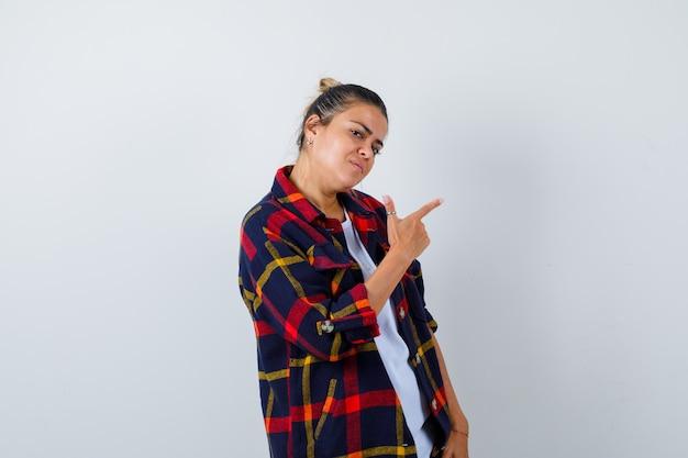 Jonge vrouw in geruit overhemd die omhoog wijst, zijwaarts staat en weemoedig kijkt.