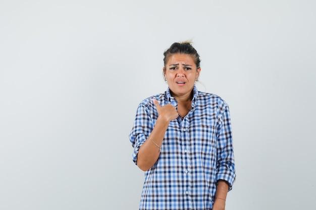 Jonge vrouw in geruit overhemd die zich richt terwijl iets vraagt en boos kijkt.