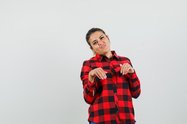 Jonge vrouw in geruit overhemd doet grappig gebaar en kijkt geamuseerd, vooraanzicht.