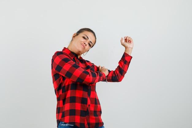 Jonge vrouw in geruit overhemd, korte broek die de spieren van de arm toont en er zelfverzekerd uitziet, vooraanzicht.