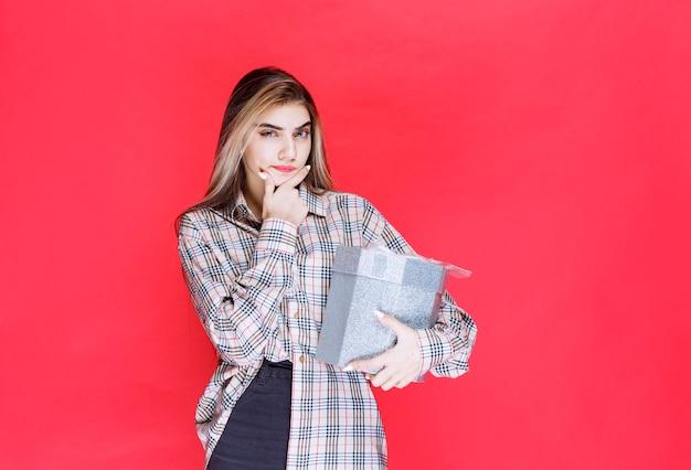 Jonge vrouw in geruit overhemd met een zilveren geschenkdoos en ziet er verward en attent uit