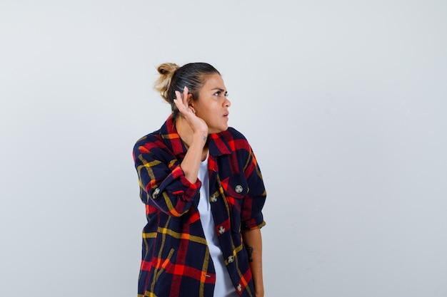 Jonge vrouw in geruit overhemd met hand achter oor, zijwaarts staande en nieuwsgierig kijkend.