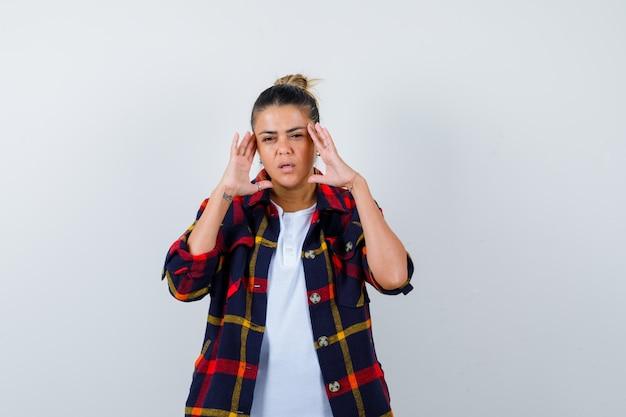 Jonge vrouw in geruit overhemd met handen op hoofd en weemoedig, vooraanzicht.