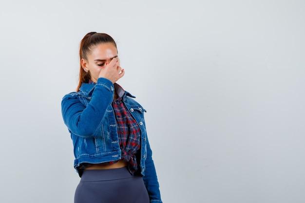 Jonge vrouw in geruit overhemd, spijkerjasje met hand op gezicht, ogen sluiten en er moe uitzien.