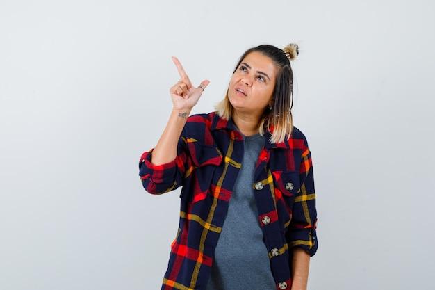 Jonge vrouw in geruit overhemd wijzend naar de linkerbovenhoek en zelfverzekerd kijkend