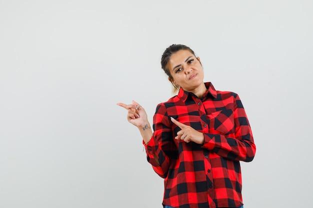Jonge vrouw in geruit overhemd wijzend naar de linkerhoek en kijkt zelfverzekerd, vooraanzicht.