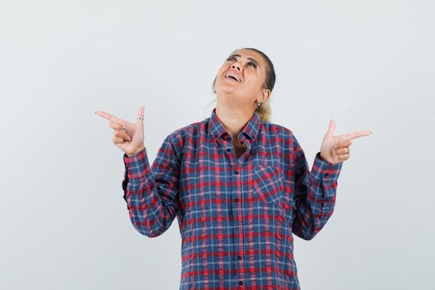 Jonge vrouw in geruit overhemd wijzend op verschillende richtingen met wijsvingers en kijkt gelukkig, vooraanzicht.