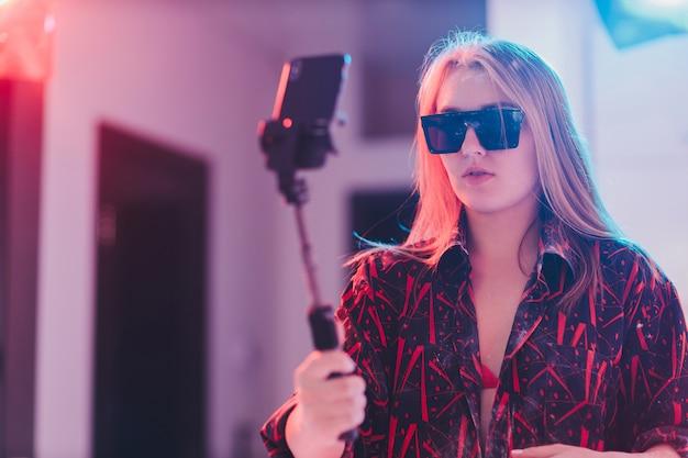 Jonge vrouw in geruite overhemd selfie te nemen