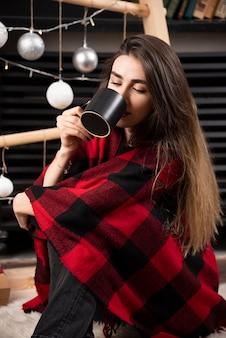 Jonge vrouw in geruite plaid die een warme kop drank drinkt.