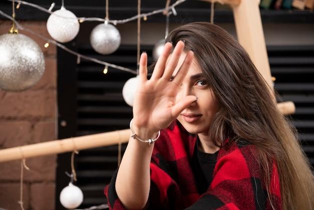 Jonge vrouw in geruite plaid poseren in de buurt van kerstballen.