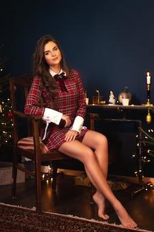 Jonge vrouw in geruite warme jurk zit naast een open haard