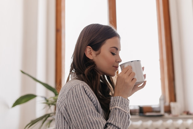 Jonge vrouw in gestreept overhemd drinkt koffie uit ijzeren beker tegen raam