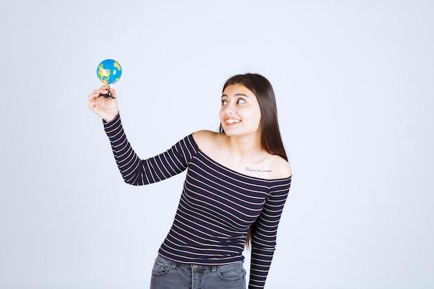 Jonge vrouw in gestreept overhemd met een minibol en kijkt opgewonden