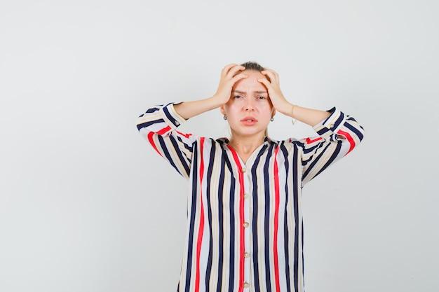 Jonge vrouw in gestreepte blouse die haar hoofd met beide handen behandelt en beklemtoond kijkt