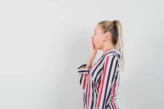 Jonge vrouw in gestreepte blouse die haar mond behandelt met één hand en geschokt kijkt