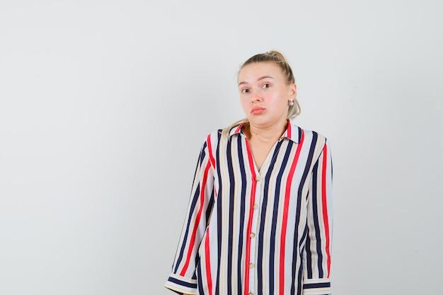 Jonge vrouw in gestreepte blouse die haar schouders ophaalt en besluiteloos kijkt