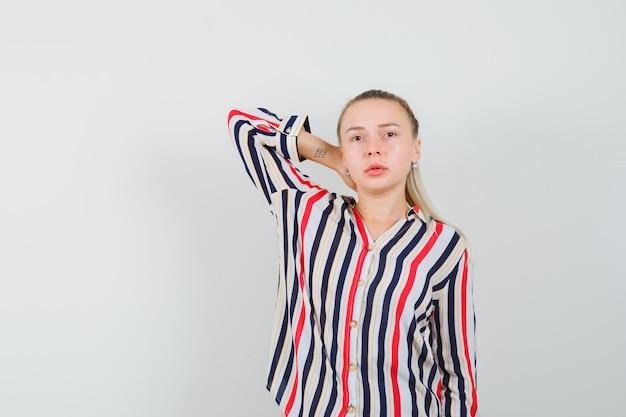 Jonge vrouw in gestreepte blouse die haar wapen achter hoofd zet en mooi kijkt