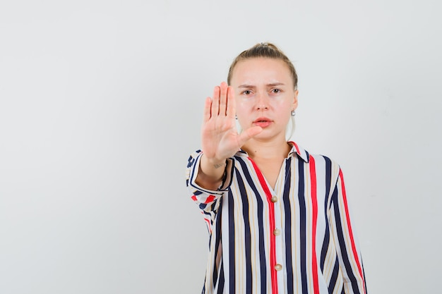 Jonge vrouw in gestreepte blouse die stopbord toont en boos kijkt