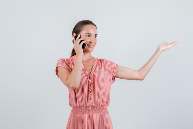 Jonge vrouw in gestreepte jurk praten over de telefoon met palm opzij gespreid, vooraanzicht.