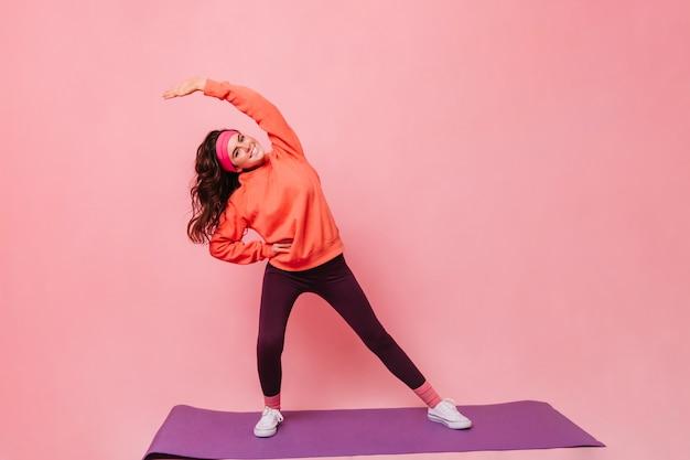 Jonge vrouw in geweldige bui doet yoga op paarse fitness mat
