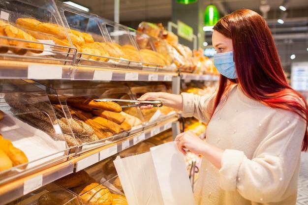 Jonge vrouw in gezicht beschermend medisch masker voor bescherming tegen virusziekte brood kopen bij kruidenier of supermarkt.