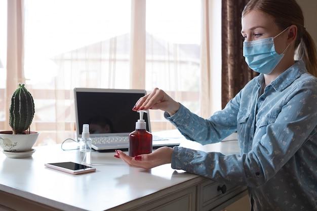 Jonge vrouw in gezichtsmasker die gadgetsoppervlakken op haar werkplaats desinfecteren