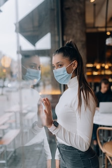 Jonge vrouw in gezichtsmasker die zich voor vensters in koffie bevindt. het meisje kijkt door het raam
