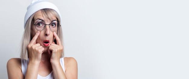 Jonge vrouw in glazen die haar vingers dichtbij het oog op een lichte achtergrond houdt. banier.