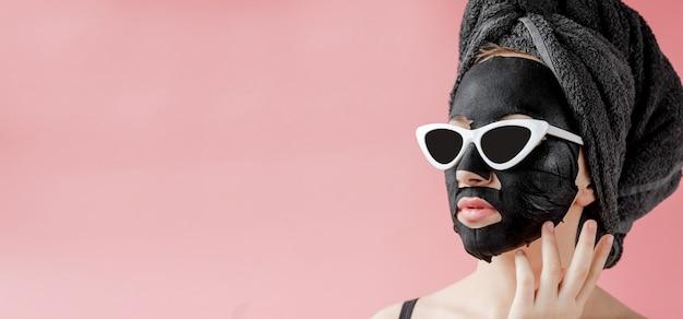 Jonge vrouw in glazen die zwart kosmetisch stoffen gezichtsmasker op roze aanbrengen
