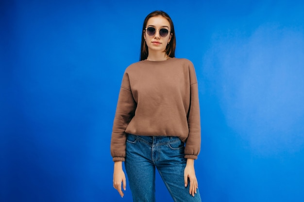 Jonge vrouw in glazen en hoodie poseren in studio op blauwe achtergrond