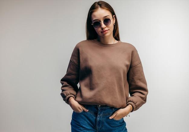 Jonge vrouw in glazen en hoodie poseren