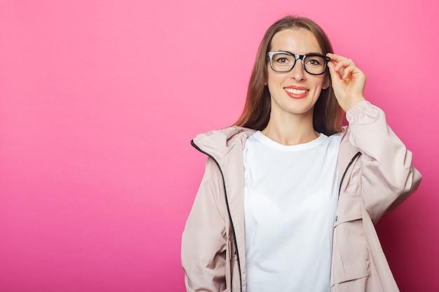 Jonge vrouw in glazen en roze jasje, roze geïsoleerde achtergrond.