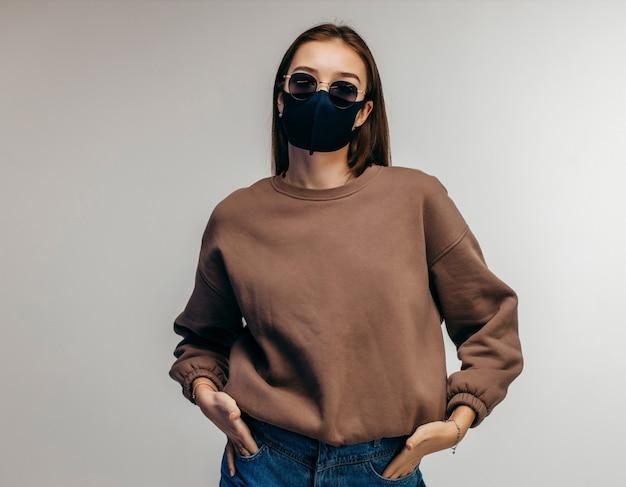 Jonge vrouw in glazen, medische masker en hoodie poseren